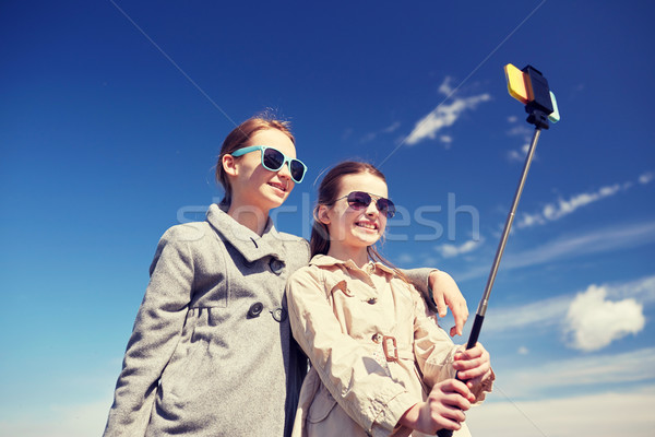 happy girls with smartphone selfie stick Stock photo © dolgachov