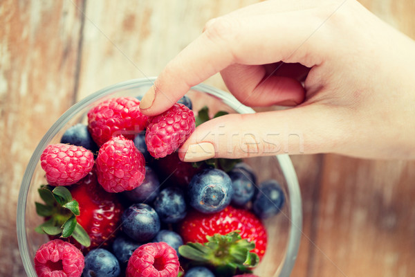 close up of woman hands with berries in glass bowl Stock photo © dolgachov