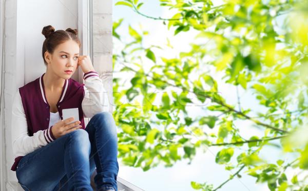teenage girl sitting on windowsill with smartphone Stock photo © dolgachov