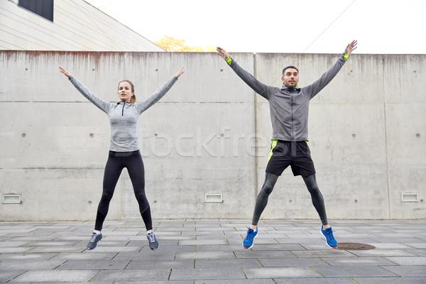 happy man and woman jumping outdoors Stock photo © dolgachov