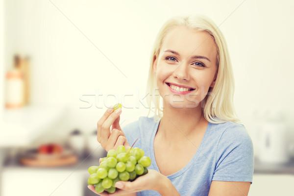 Boldog nő eszik szőlő konyha egészséges étkezés Stock fotó © dolgachov