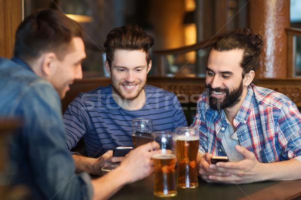 Mannelijke vrienden smartphones drinken bier bar Stockfoto © dolgachov