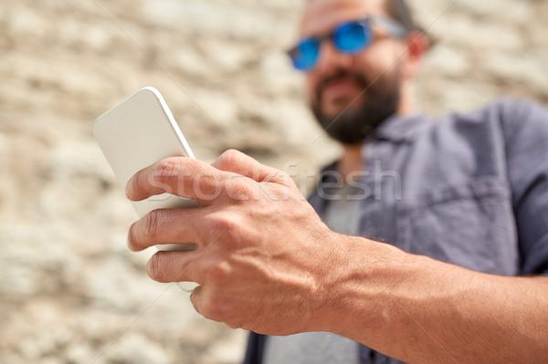 Człowiek smartphone mur wypoczynku technologii Zdjęcia stock © dolgachov