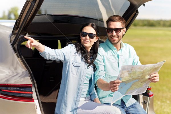 Stock photo: happy man and woman with road map at hatchback car