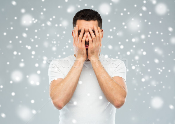 man covering his face with hands over snow Stock photo © dolgachov