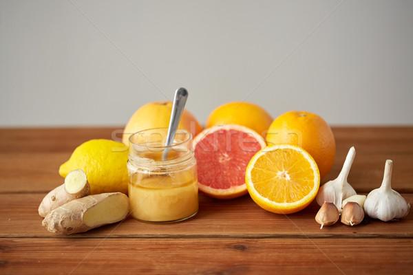 honey, citrus fruits, ginger and garlic on wood Stock photo © dolgachov