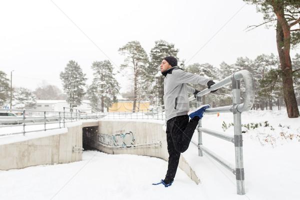 sports man stretching leg at fence in winter Stock photo © dolgachov