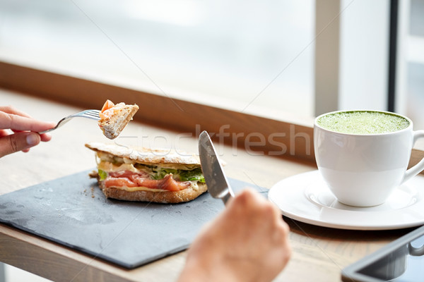 Stock photo: woman eating salmon panini sandwich at restaurant