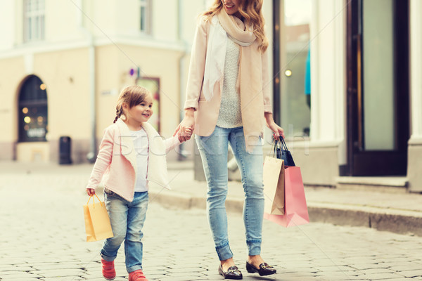 happy mother and child with shopping bags in city Stock photo © dolgachov