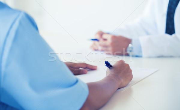 close up of doctor taking notes at hospital Stock photo © dolgachov