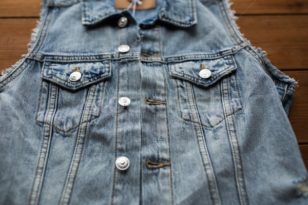 close up of denim vest or waistcoat on wood Stock photo © dolgachov