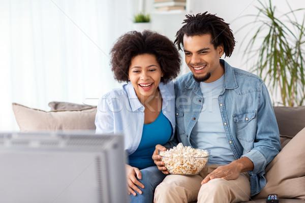 улыбаясь пару попкорн смотрят телевизор домой Сток-фото © dolgachov