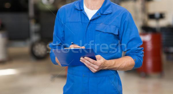 mechanic man with clipboard at car workshop Stock photo © dolgachov