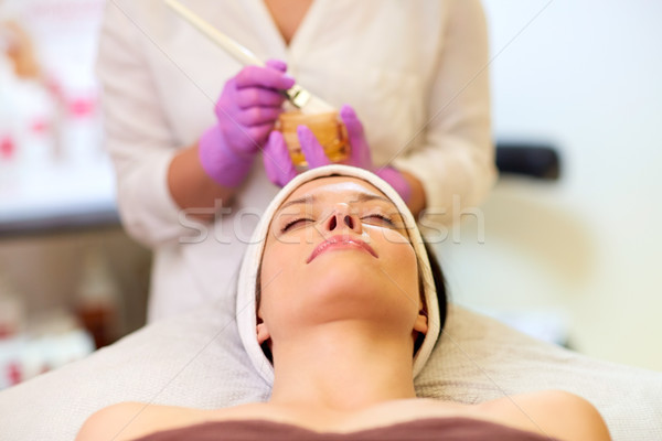 beautician applying facial mask to woman at spa Stock photo © dolgachov
