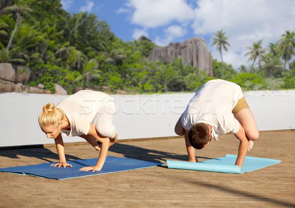 couple making yoga crow pose over tropical beach Stock photo © dolgachov