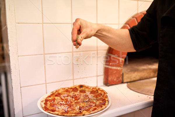 cook adding pepper to salami pizza at pizzeria Stock photo © dolgachov