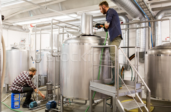 men working at craft beer brewery kettles Stock photo © dolgachov