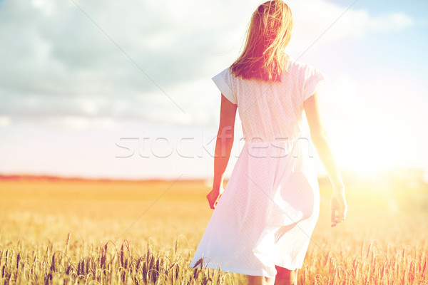 young woman in white dress walking along on field Stock photo © dolgachov