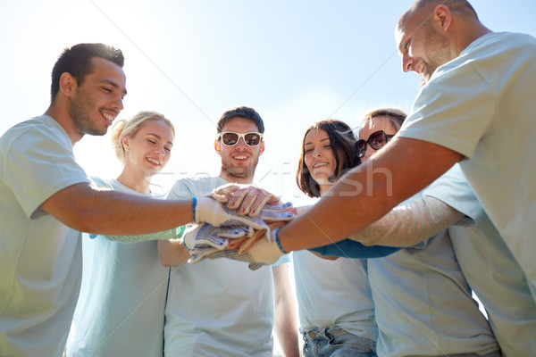 group of volunteers putting hands on top outdoors Stock photo © dolgachov