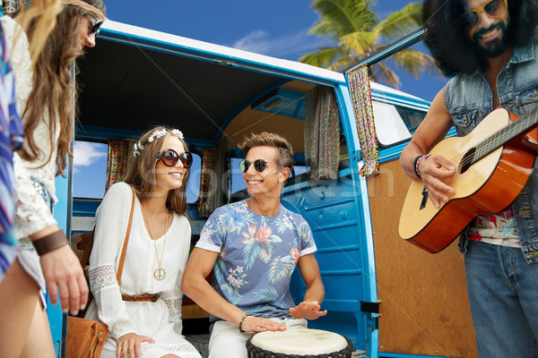 hippie friends playing music over minivan on beach Stock photo © dolgachov