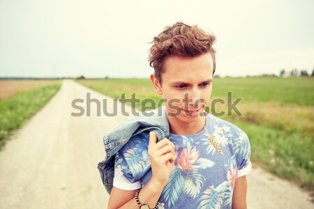 sad young hippie man walking along country road Stock photo © dolgachov