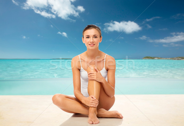 beautiful woman touching her smooth legs on beach Stock photo © dolgachov