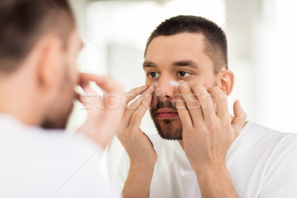 young man applying cream to face at bathroom Stock photo © dolgachov