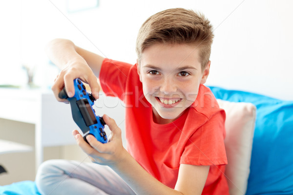 happy boy with gamepad playing video game at home Stock photo © dolgachov