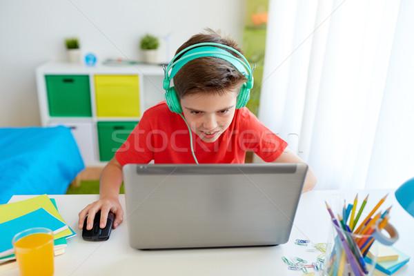Nino auriculares jugando videojuegos portátil Foto stock © dolgachov