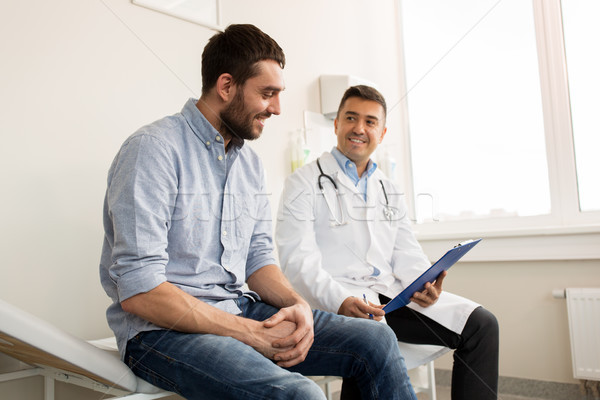 smiling doctor and young man meeting at hospital Stock photo © dolgachov
