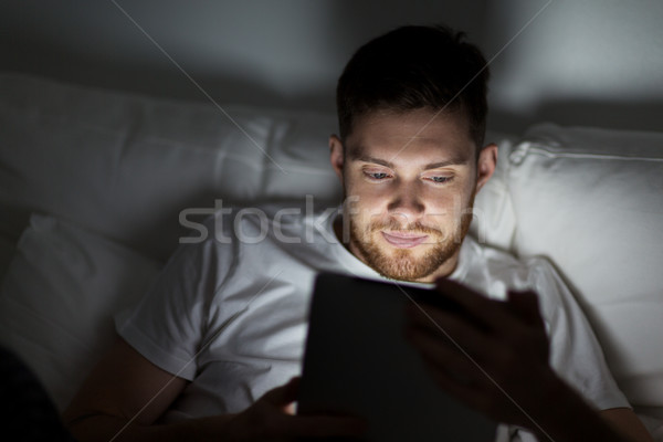 young man with tablet pc in bed at home bedroom Stock photo © dolgachov