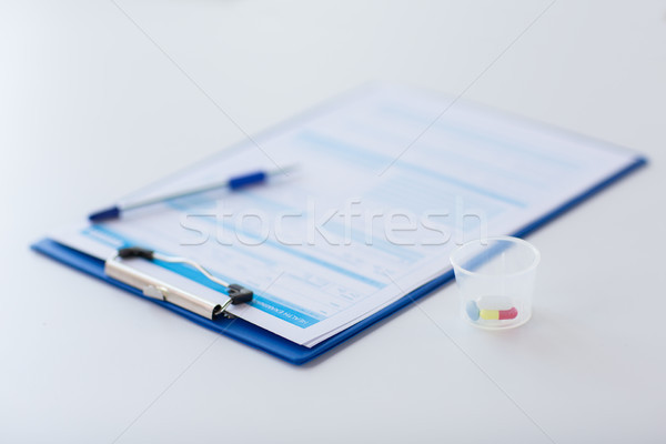 clipboard with report and drugs in medical cup Stock photo © dolgachov