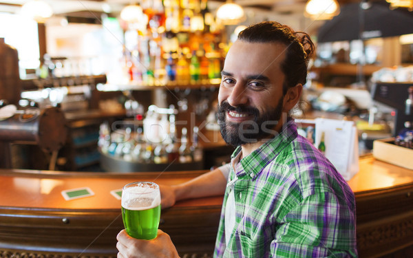 man drinking green beer at bar or pub Stock photo © dolgachov