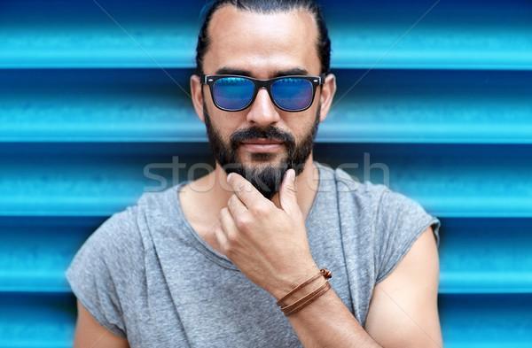 close up of man in sunglasses touching beard Stock photo © dolgachov