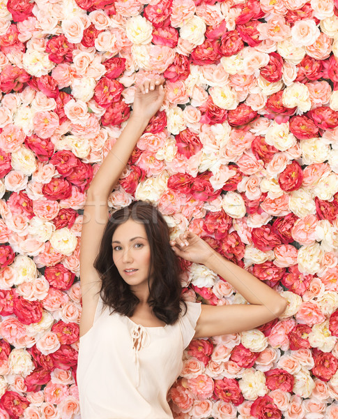 young woman with background full of roses Stock photo © dolgachov