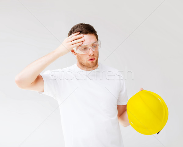 Stock photo: male builder in safety glasses taking off helmet