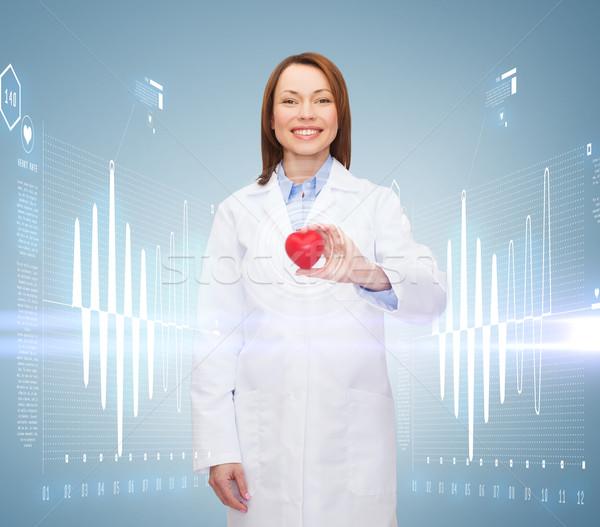 smiling female doctor with heart Stock photo © dolgachov