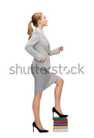 smiling businesswoman stepping on pile of books Stock photo © dolgachov