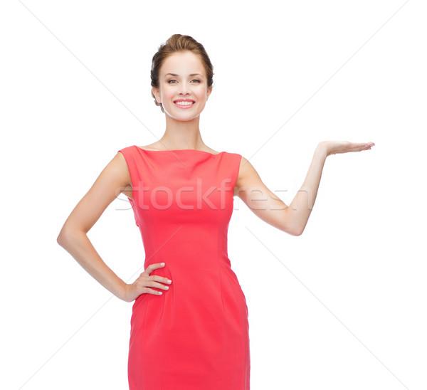 Femme souriante quelque chose imaginaire Palm publicité Photo stock © dolgachov