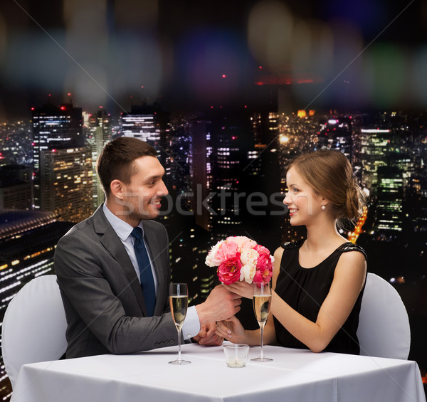 smiling man giving flower bouquet to woman Stock photo © dolgachov