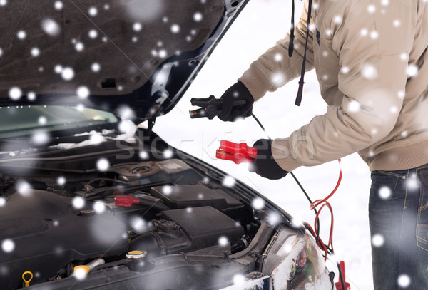Stock photo: closeup of man under bonnet with starter cables