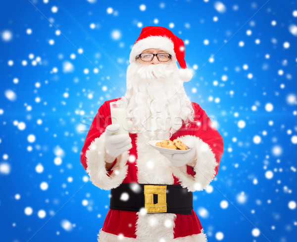 santa claus with glass of milk and cookies Stock photo © dolgachov
