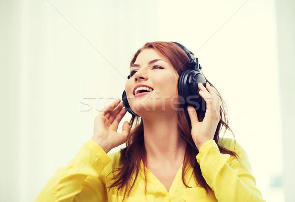 Sorridente jovem fones de ouvido casa tecnologia música Foto stock © dolgachov