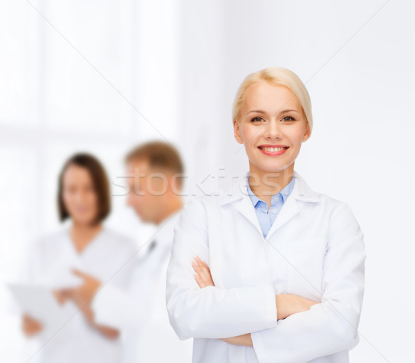 smiling female doctor with group of medics Stock photo © dolgachov