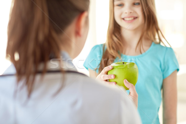 close up of doctor giving apple to happy girl Stock photo © dolgachov