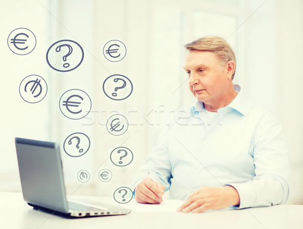 Stock photo: old man with laptop filling a form at home