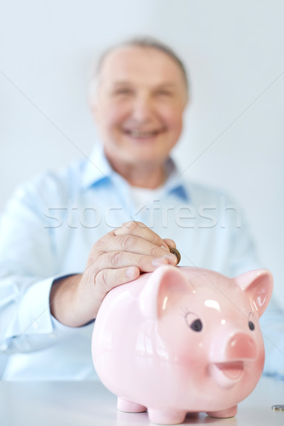 close up of old man putting coin into piggybank Stock photo © dolgachov