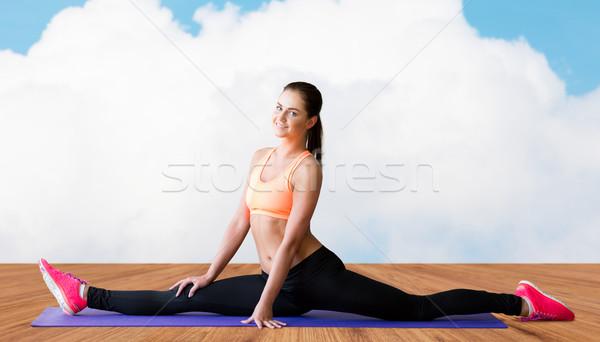 smiling woman doing splits on mat over cloud Stock photo © dolgachov