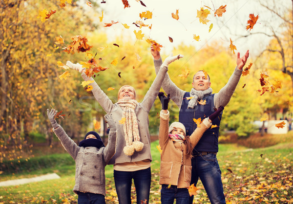 Stock photo: happy family playing with autumn leaves in park