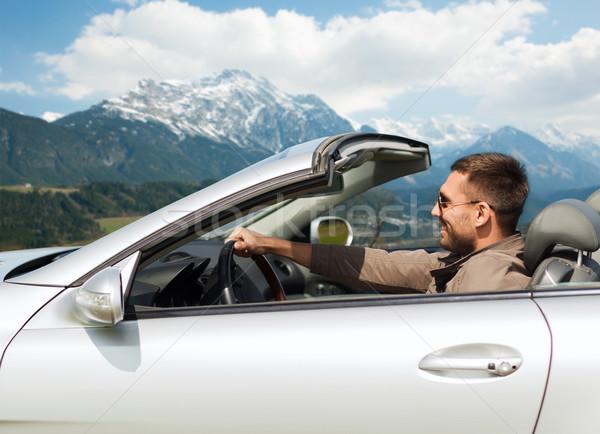 Feliz homem condução cabriolé carro montanhas Foto stock © dolgachov